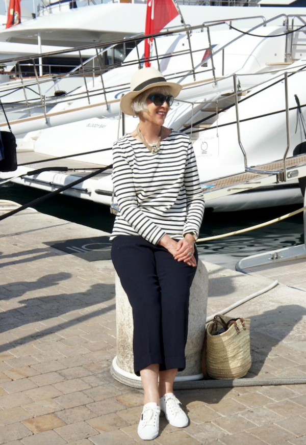 Breton sweater seated by large yacht