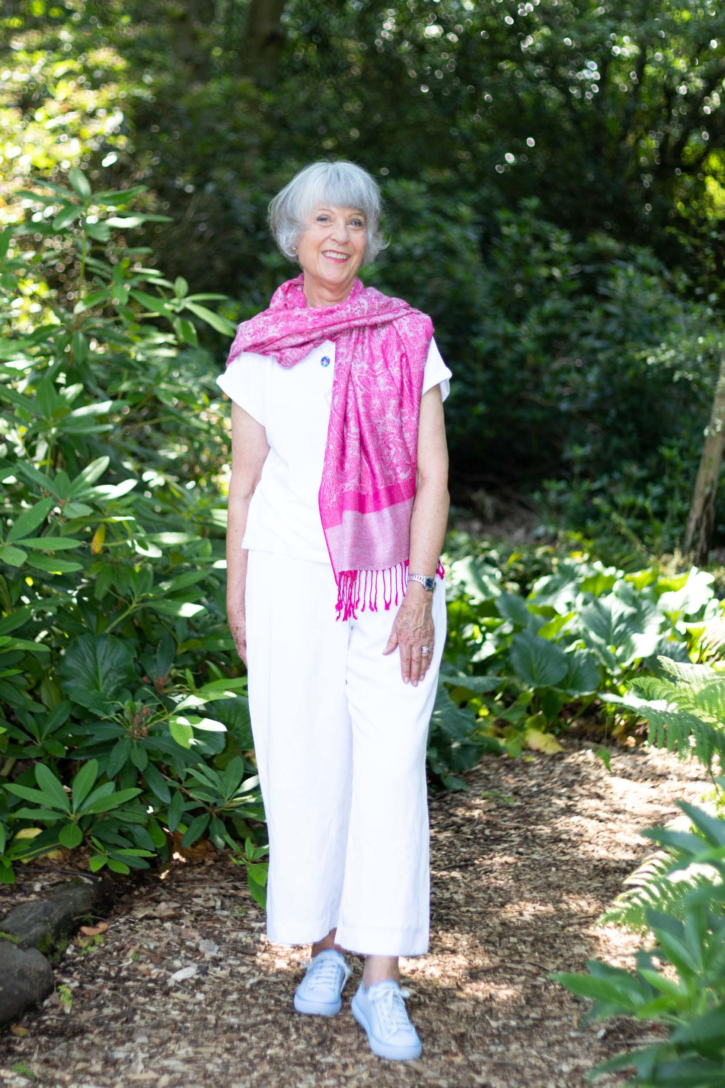 White tee shirt with trousers and bright pink scarf.