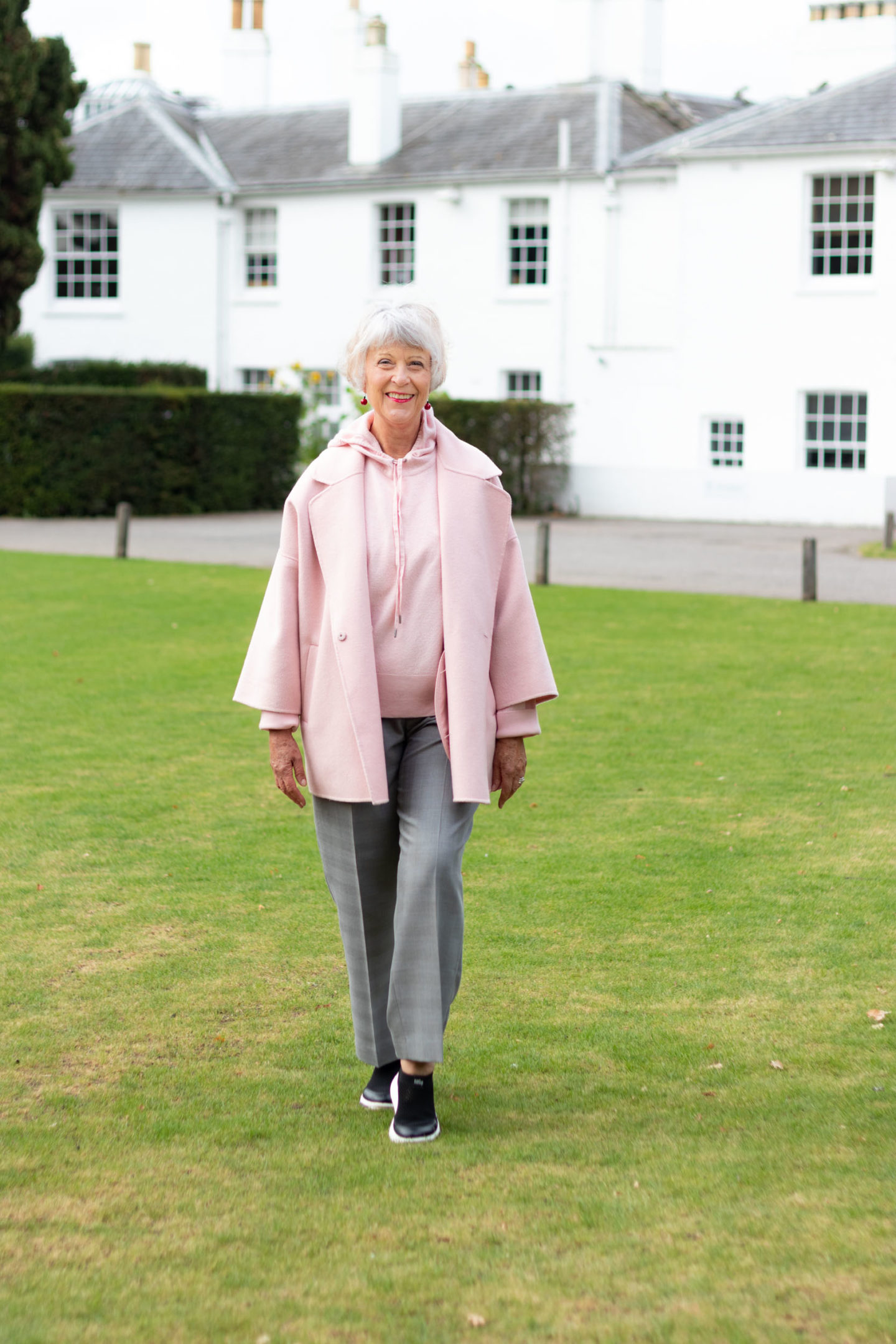 Pink coat, pink hoodie and grey trousers
