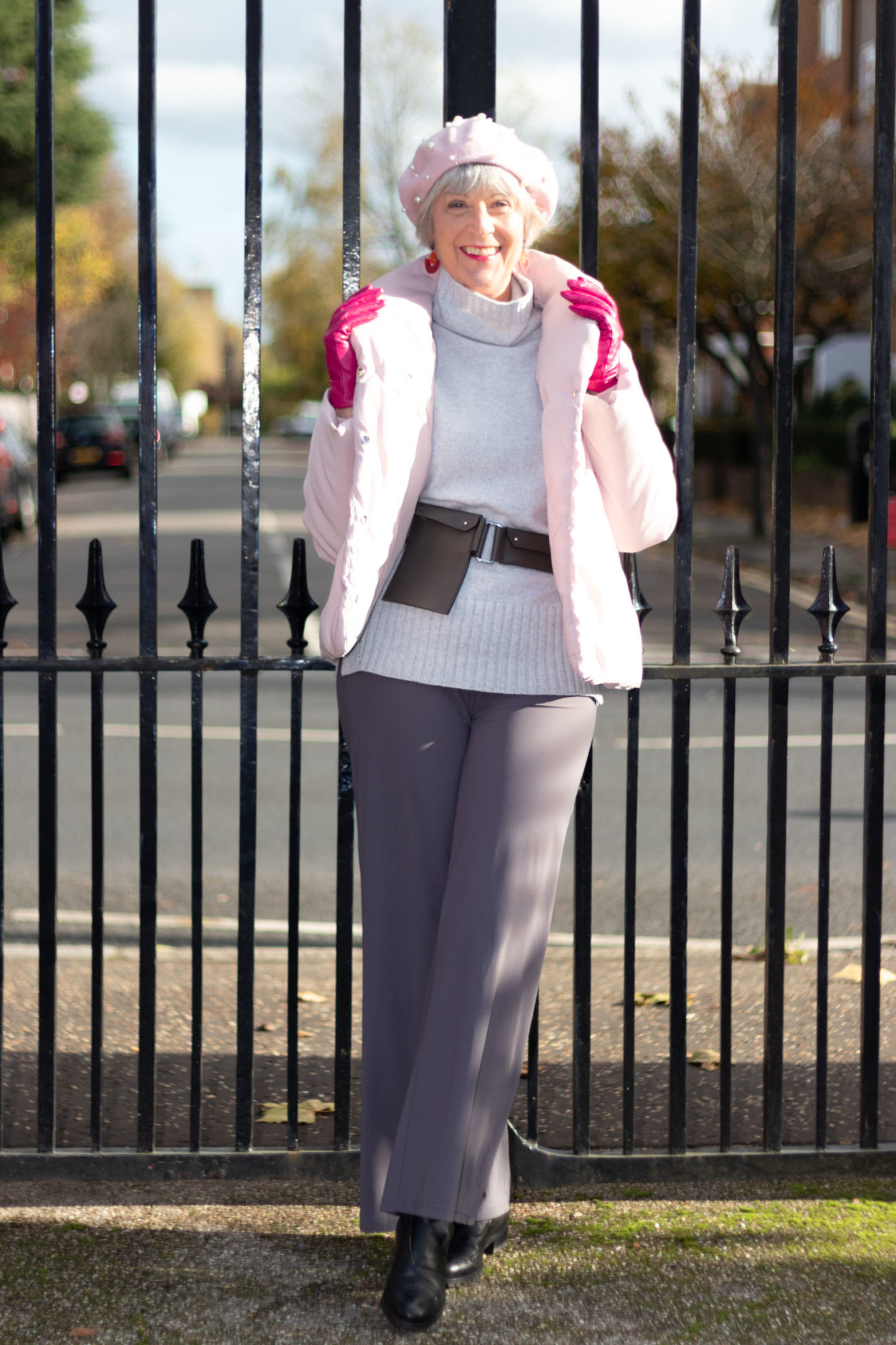 pink puffer jacket, grey sweater and grey trousers