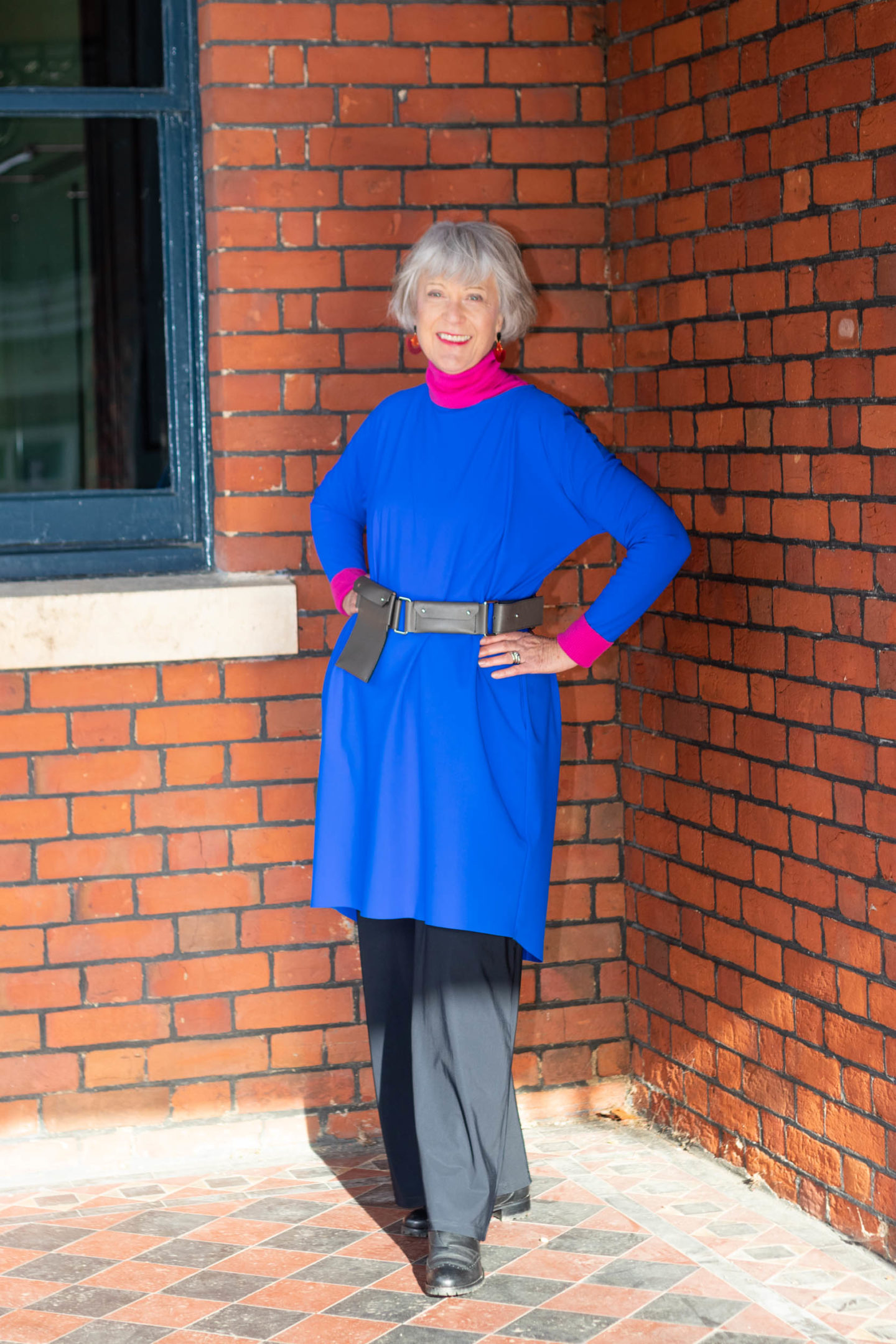 Bright blue dress, pink rollback and black trousers