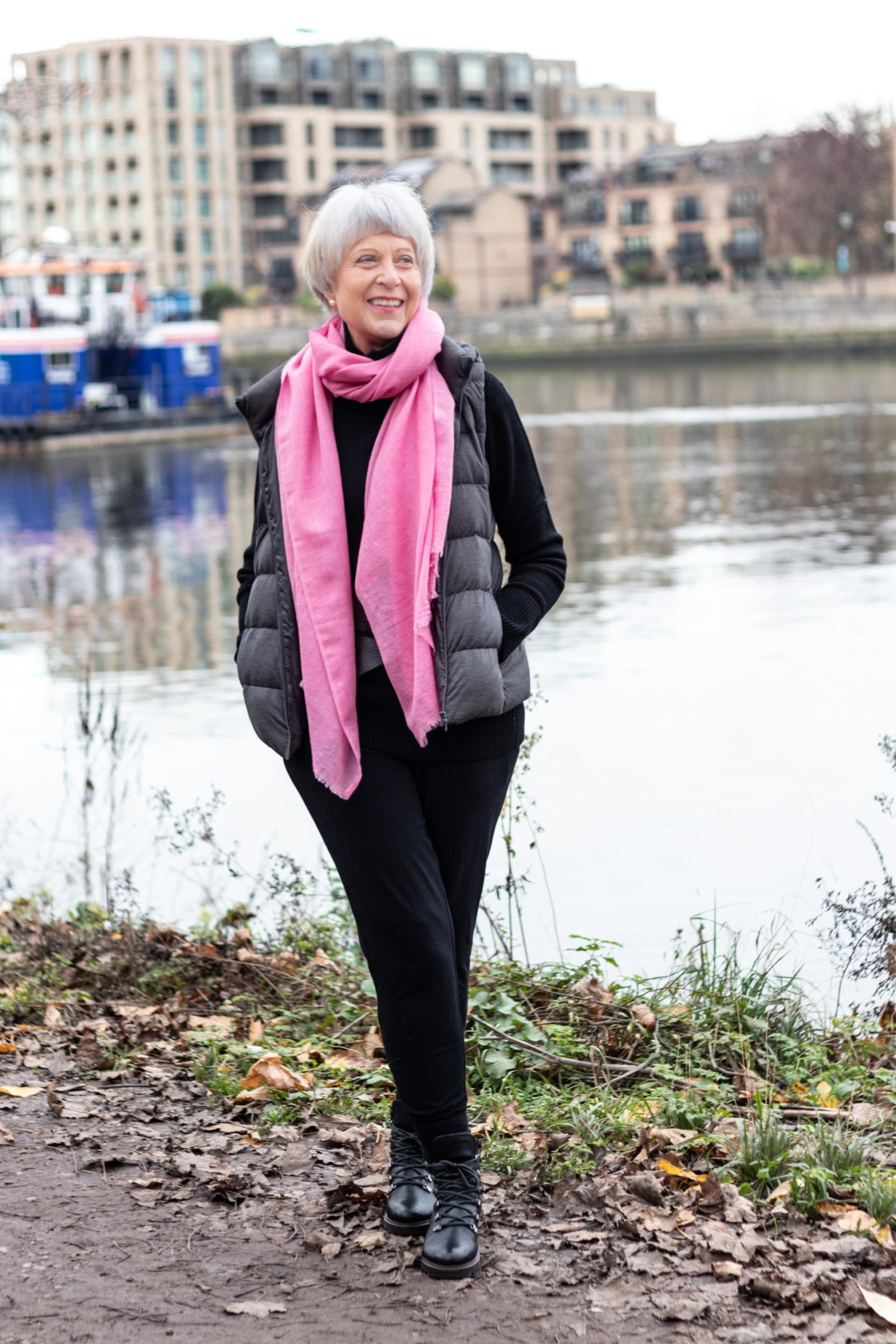 Black polo neck,  Grey sleeveless puffer and pink scarf.