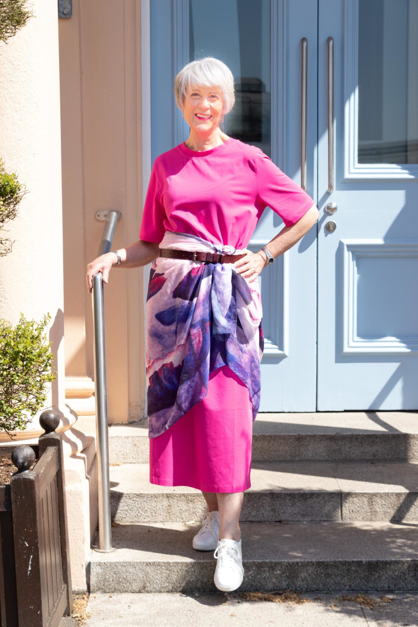 Pink tee shirt maxi dress accessorised with a colourful scarf